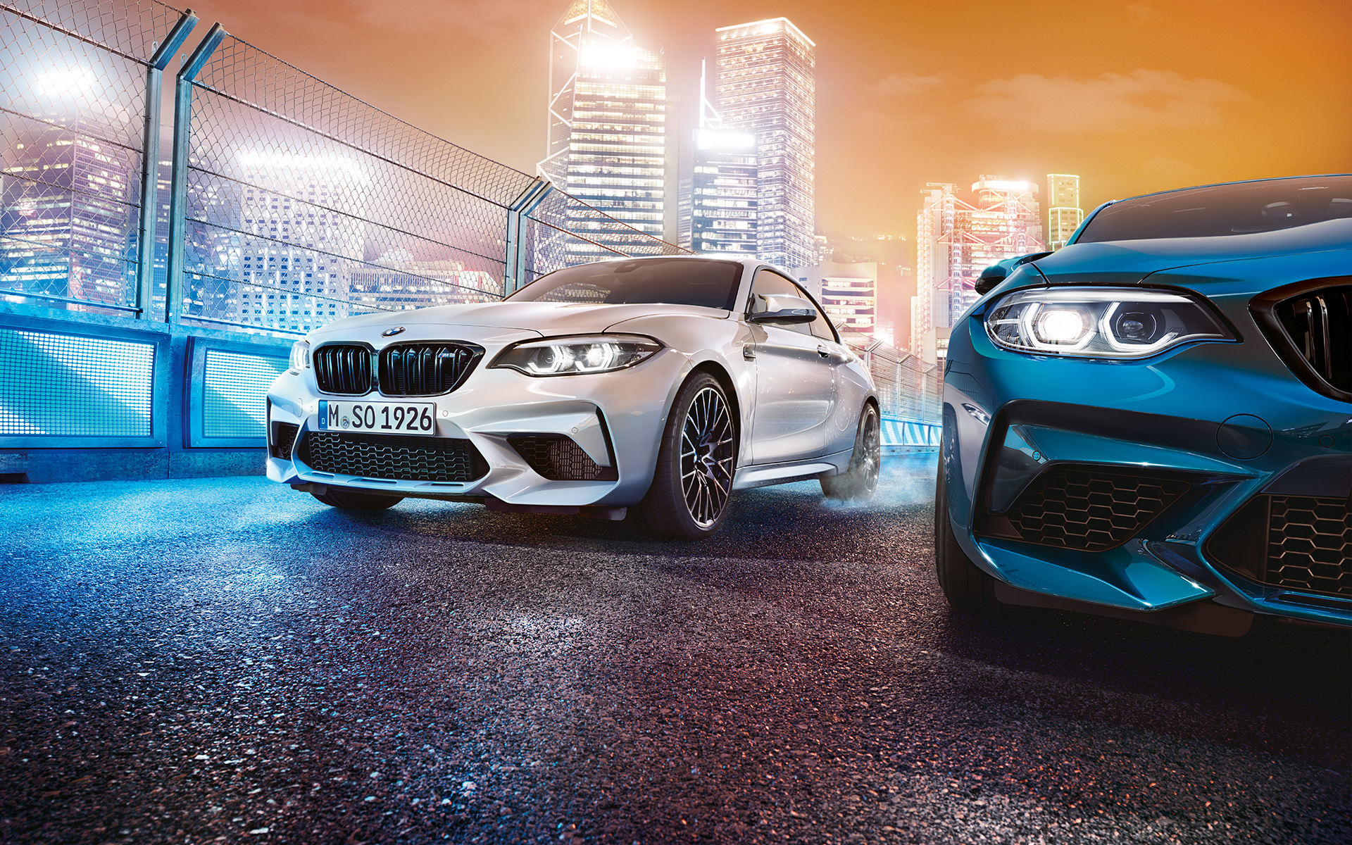 White and blue BMW M2 Competition in front view standing in front of nocturnal cityscape.
